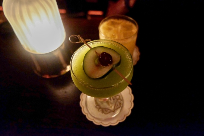 Up close of a cocktail decorated with a cucumber and cherry, on a candlelit table