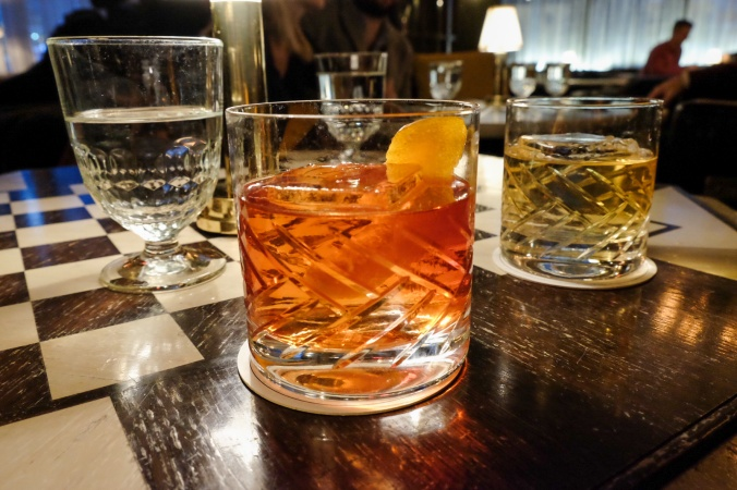 Glass tumbler with negroni and a whiskey in the background