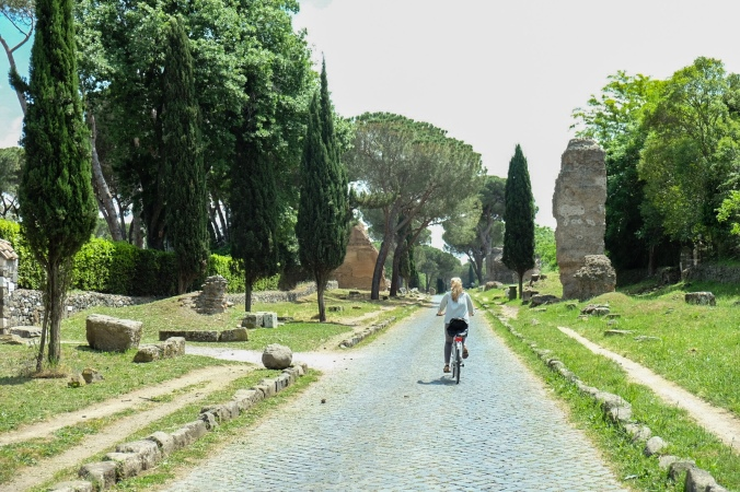 Biking along the Appia Antica with greenery and ruins surrounding